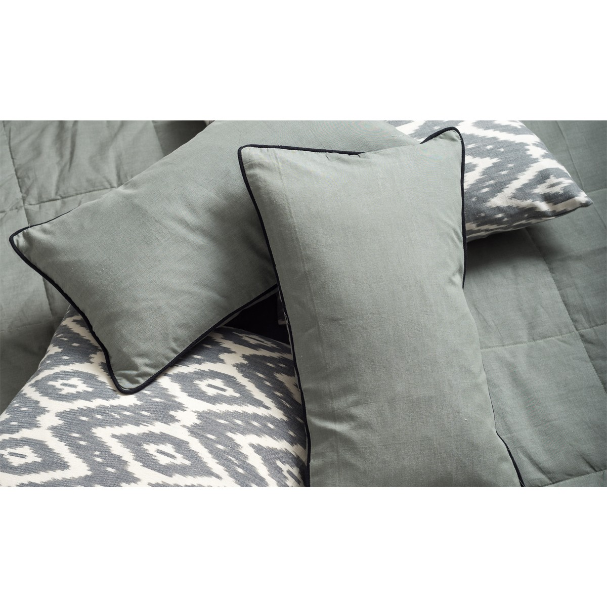 Single grey cushion cover with black piping